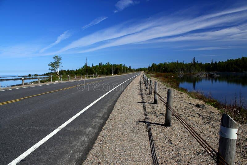 Ατελείωτος δρόμος - δρόμος οδηγεί μέσω της όμορφης αγροτικής γεωργικής γης - οριζόντιος πλαισιωμένος πυροβολισμός στοκ φωτογραφίες