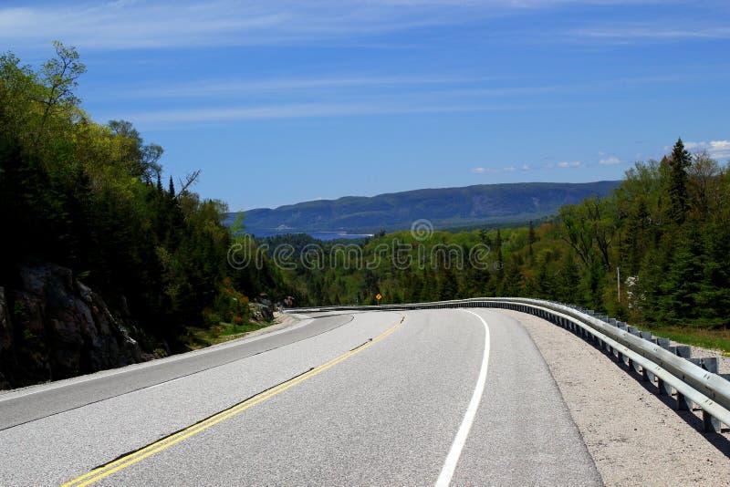 Ατελείωτος δρόμος - δρόμος οδηγεί μέσω της όμορφης αγροτικής γεωργικής γης - οριζόντιος πλαισιωμένος πυροβολισμός στοκ εικόνες