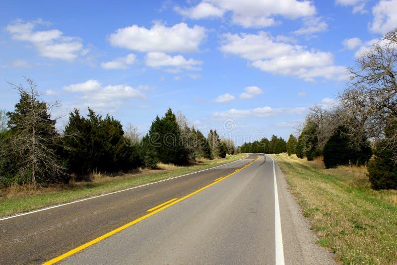 Ατελείωτος δρόμος - δρόμος οδηγεί μέσω της όμορφης αγροτικής γεωργικής γης - οριζόντιος πλαισιωμένος πυροβολισμός στοκ εικόνες με δικαίωμα ελεύθερης χρήσης
