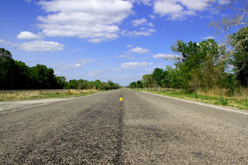 Ατελείωτος δρόμος - δρόμος οδηγεί μέσω της όμορφης αγροτικής γεωργικής γης - οριζόντιος πλαισιωμένος πυροβολισμός στοκ εικόνα