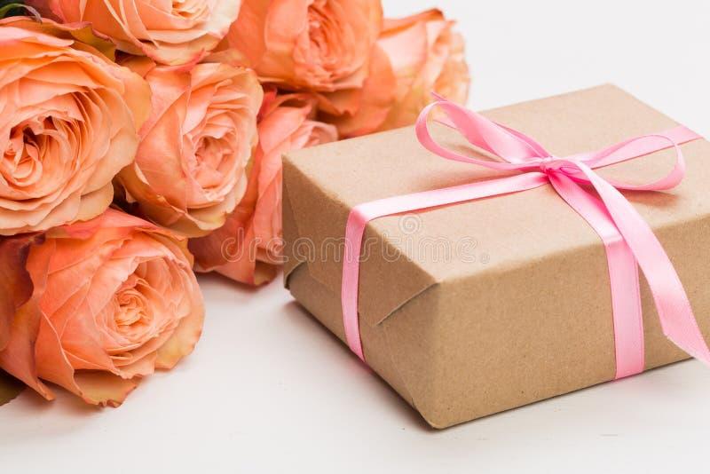 Αυξήθηκε τριαντάφυλλα με το παρόν στο ρόδινο υπόβαθρο, ημέρα της μητέρας, ημέρα της γυναίκας στοκ εικόνες