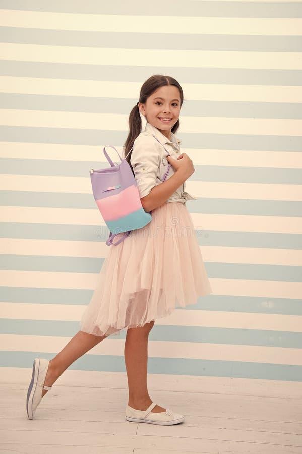 Απλά cuteness Το χαριτωμένο πρόσωπο χαμόγελου κοριτσιών παιδιών φέρνει την τσάντα στον ώμο Μοντέρνη εξάρτηση ένδυσης τρίχας παιδι στοκ εικόνα με δικαίωμα ελεύθερης χρήσης