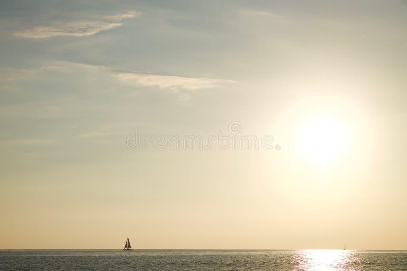 Βάρκα πανιών στον ορίζοντα στο ηλιοβασίλεμα στοκ φωτογραφία