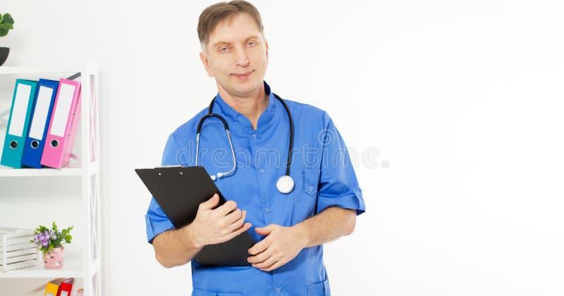Βέβαιος χαμογελώντας γιατρός που θέτει και που εξετάζει τη κάμερα με το μαύρο φάκελλο, ιατρική κλινική γραφείων στο υπόβαθρο, διά στοκ φωτογραφία