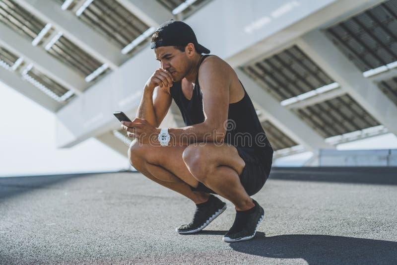Βέβαιο μυϊκό κατάλληλο αθλητικό πρότυπο sprinter που στηρίζεται μετά από το workout του και που χρησιμοποιεί το κινητό τηλέφωνο γ στοκ εικόνα
