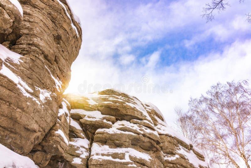 Βαλμένοι σε στρώσεις γρανίτης βράχοι, που καλύπτονται με το χιόνι ενάντια στο μπλε ουρανό στοκ φωτογραφίες