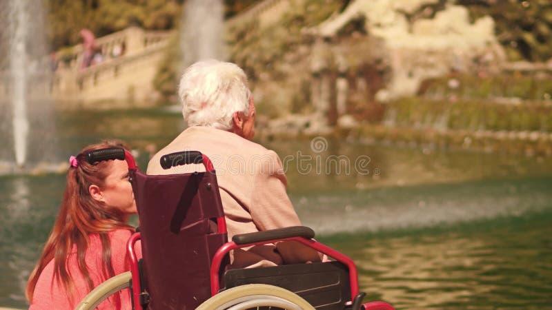 ΒΑΡΚΕΛΩΝΗ, ΙΣΠΑΝΙΑΣ - 16 ΑΠΡΙΛΙΟΥ, 2017 Ανάπηρη ανώτερη γυναίκα σε μια αναπηρική καρέκλα και η κόρη της κοντά στην πηγή πάρκων στοκ φωτογραφίες