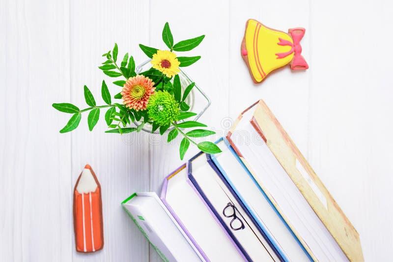 Βιβλία, γυαλιά σελιδοδεικτών, μολύβι μελοψωμάτων και κίτρινο κουδούνι, χρυσάνθεμο σε ένα άσπρο ξύλινο υπόβαθρο στοκ εικόνες με δικαίωμα ελεύθερης χρήσης