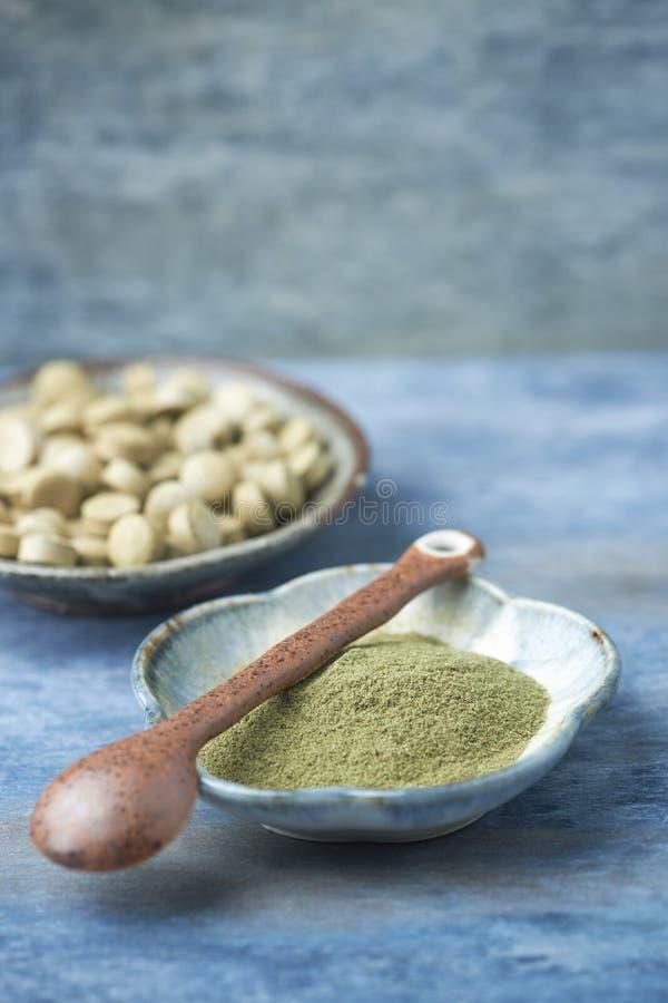 Βιο πράσινες σκόνη και ταμπλέτες ΧΛΟΗΣ ΚΡΙΘΑΡΙΟΥ Έννοια για μια υγιή διαιτητική συμπλήρωση στοκ εικόνες
