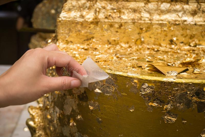 Βουδιστικός κρατά το χρυσό έγγραφο που κολλά στην επιφάνεια του αγάλματος του Βούδα στοκ εικόνες