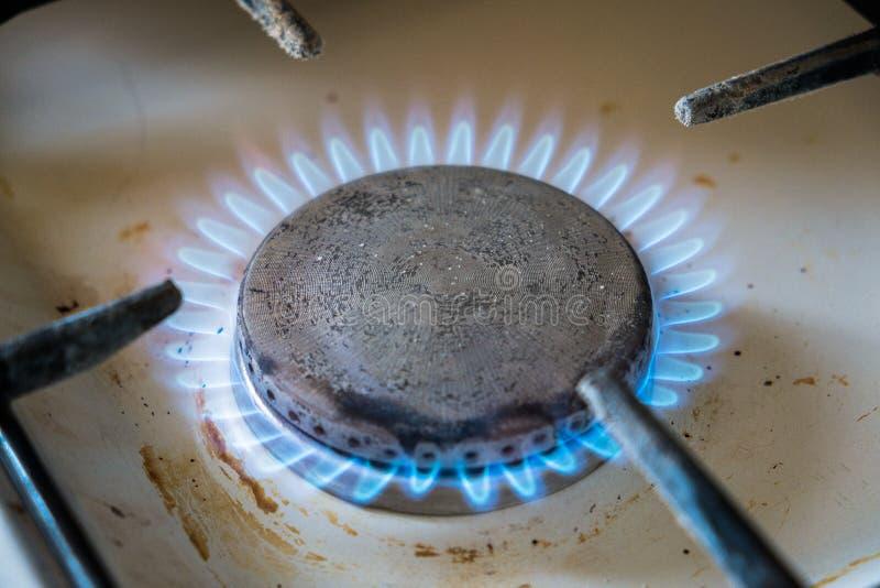 Βρώμικος παλαιός καυστήρας αερίου κουζινών Τεμάχιο μιας σόμπας αερίου, φωτεινή μπλε φλόγα στοκ φωτογραφία με δικαίωμα ελεύθερης χρήσης