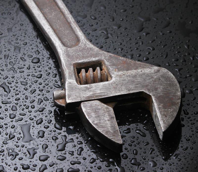Γαλλικό κλειδί σε μια μαύρη ανασκόπηση στοκ φωτογραφία