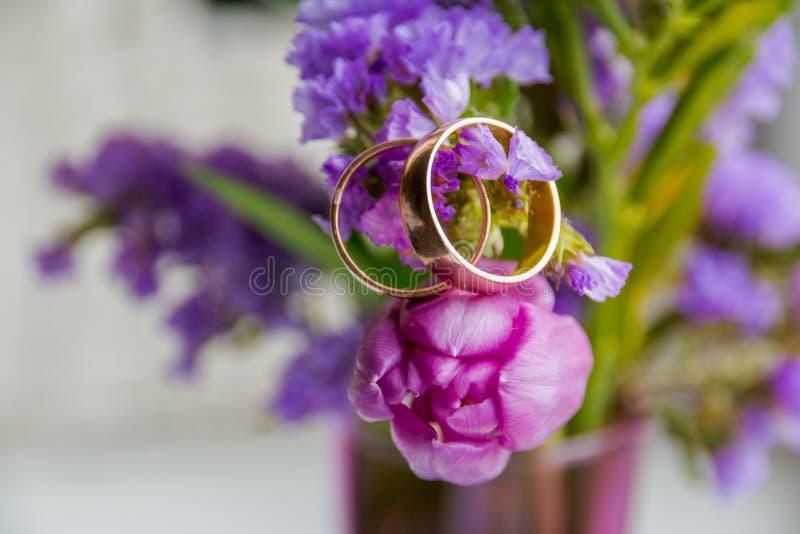Γαμήλια έννοια: ανθοδέσμη ρόδινων, πορφυρών τουλιπών και δύο χρυσών δαχτυλιδιών Ανθίζοντας κλάδος με τα πορφυρά, ιώδη λουλούδια ε στοκ εικόνες