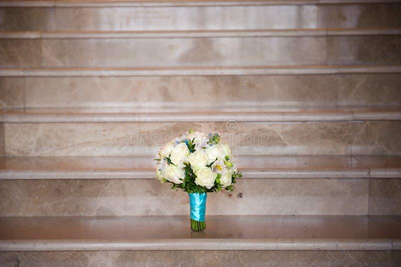 Γαμήλια ανθοδέσμη των τριαντάφυλλων στα βήματα ενός γρανίτη στοκ εικόνα