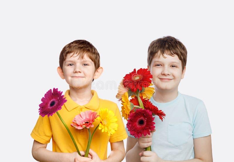 Γελώντας αγόρι με τα λουλούδια gerbera ανθοδεσμών στοκ εικόνες
