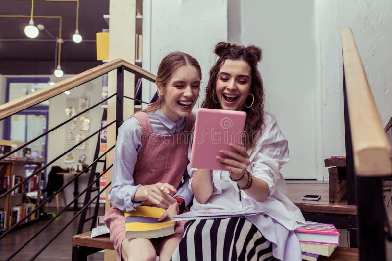 Γελώντας ελκυστικές κυρίες που παρατηρούν τη στοά στην ταμπλέτα και τη συζήτηση των φωτογραφιών στοκ εικόνα