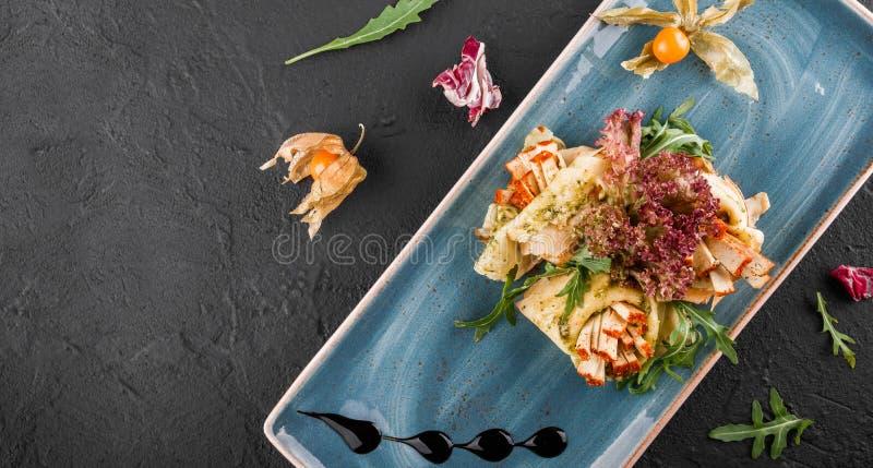 Γεμισμένος crepes ολοκληρωμένος με tofu το τυρί, τη σάλτσα pesto και το arugula στο πιάτο Άποψη σχετικά με μια σκοτεινή γκρίζα επ στοκ εικόνες με δικαίωμα ελεύθερης χρήσης