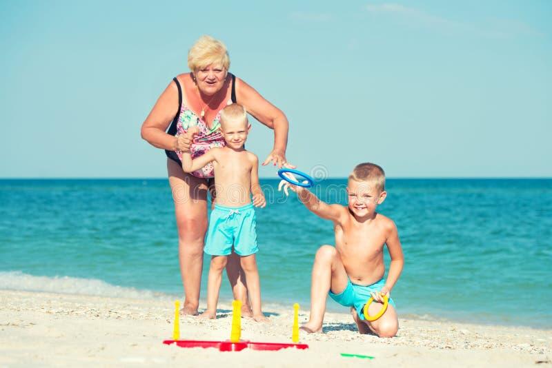 Γιαγιά με τα εγγόνια που παίζουν ένα παιχνίδι που ρίχνει τα δαχτυλίδια στην παραλία στοκ φωτογραφία