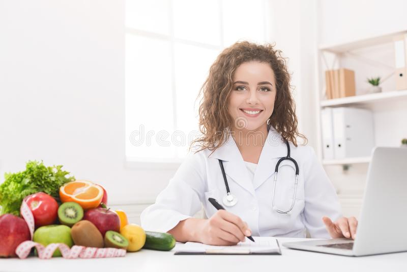 Γιατρός που εργάζεται με το lap-top και που γράφει στη γραφική εργασία στοκ φωτογραφία