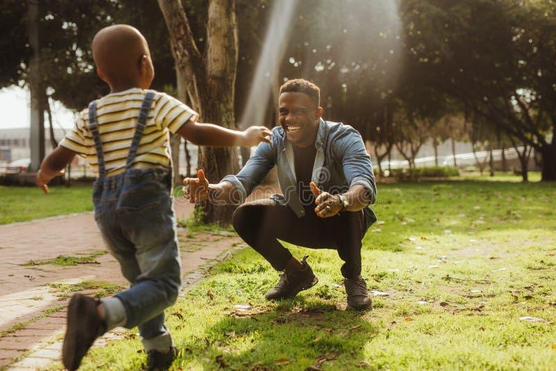 Γιος που τρέχει στον εναγκαλισμό του πατέρα στοκ φωτογραφία με δικαίωμα ελεύθερης χρήσης