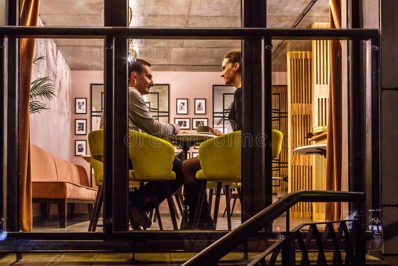 ΓΚΡΟΝΤΝΟ, ΛΕΥΚΟΡΩΣΙΑ - ΤΟ ΔΕΚΈΜΒΡΙΟ ΤΟΥ 2018: αγαπώντας ζεύγος στον καφέ επιτραπέζιας κατανάλωσης στο εσωτερικό στο μικρό σύγχρον στοκ εικόνα με δικαίωμα ελεύθερης χρήσης