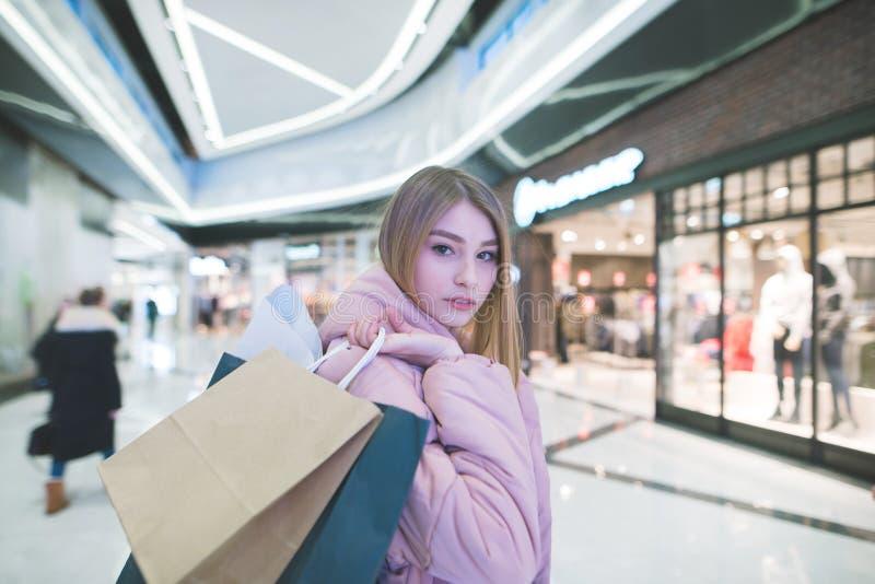 Γλυκός ξανθός με τις τσάντες αγορών στα χέρια μιας λεωφόρου που εξετάζει τη κάμερα ψωνίζοντας λευκή γυναίκα ποδιών έννοιας τσαντώ στοκ εικόνες με δικαίωμα ελεύθερης χρήσης