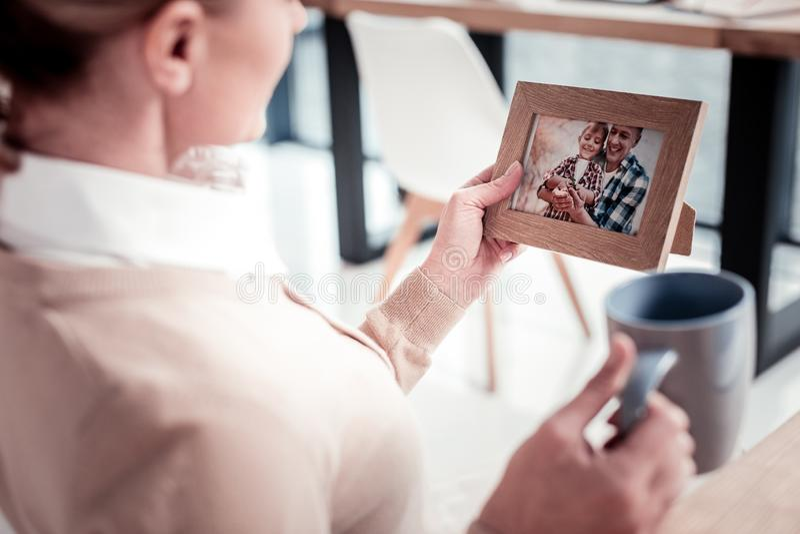 Γοητεία της ώριμης γυναίκας που κρατά το ξύλινο πλαίσιο φωτογραφιών με την οικογενειακή εικόνα της στοκ φωτογραφία με δικαίωμα ελεύθερης χρήσης