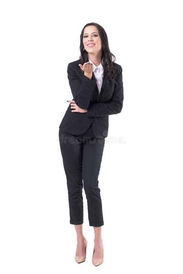 Γοητευτικός την καλή κομψή επιχειρησιακή γυναίκα που χαμογελά και που στέλνει το φιλί στη κάμερα στοκ εικόνα