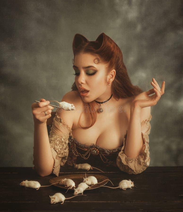 Γοητευτικός τη redhead κυρία με τα αυτιά γατών φιαγμένα από τρίχα που πηγαίνει να φάει το άσπρο ποντίκι στο δίκρανο Η κοντέσα pus στοκ εικόνες