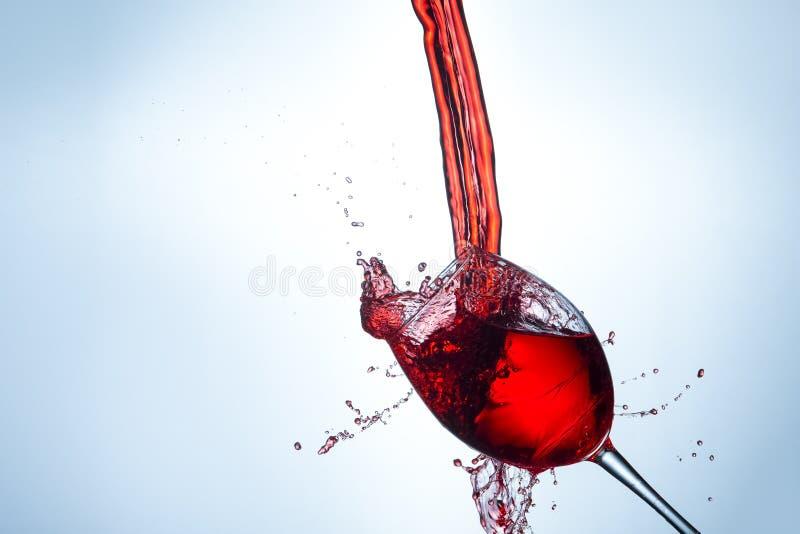 Γρήγορη φωτογραφία δράσης Ρεύματα και σταγονίδια της έκχυσης κόκκινου κρασιού έξω του σαφούς γυαλιού κρασιού στοκ εικόνα με δικαίωμα ελεύθερης χρήσης