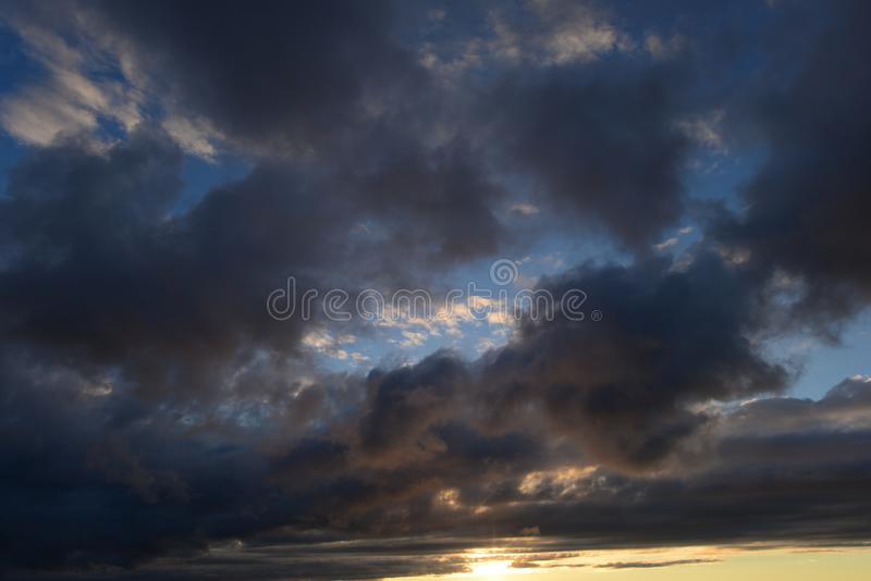 Γραφικό τοπίο του φωτεινού θυελλώδους ουρανού στο φως του ήλιου από τα σκοτεινά σύννεφα στοκ φωτογραφία με δικαίωμα ελεύθερης χρήσης