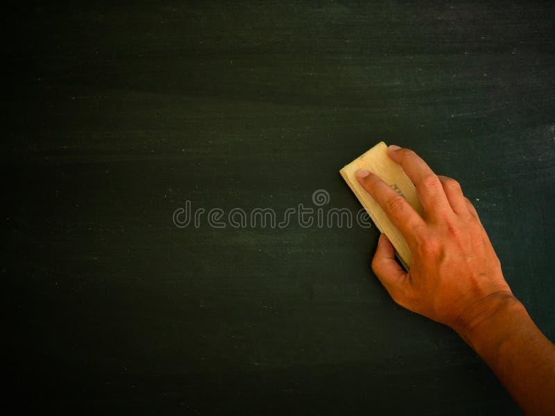 Γόμα και πίνακας βουρτσών εκμετάλλευσης χεριών στοκ φωτογραφία