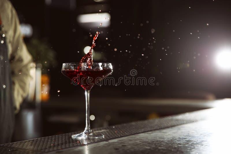 Γυαλί του ραντίσματος του κοσμοπολίτικου martini κοκτέιλ στο μετρητή φραγμών στοκ εικόνα με δικαίωμα ελεύθερης χρήσης