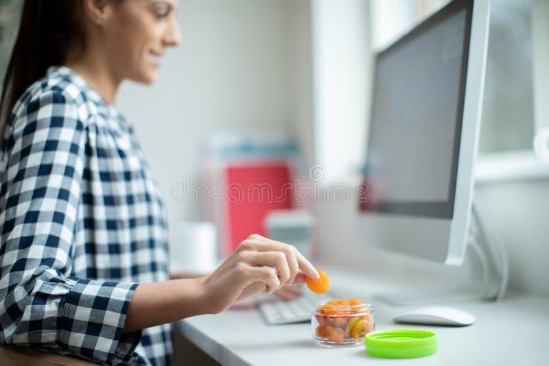Γυναίκα εργαζόμενος στην αρχή έχοντας το υγιές πρόχειρο φαγητό των ξηρών βερίκοκων στο γραφείο στοκ φωτογραφία