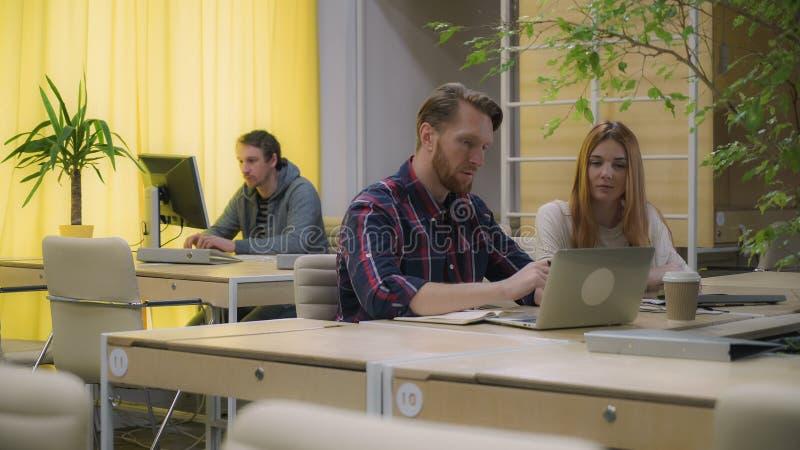 Γυναίκα και άνδρας που συζητούν τις επιχειρησιακές διαδικασίες, γραφείο ανοιχτού χώρου στοκ εικόνα