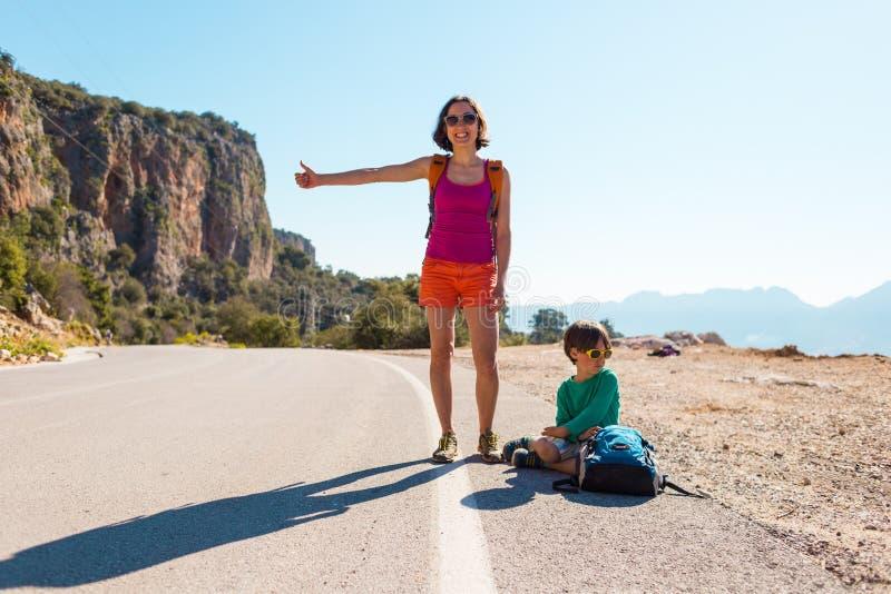 Γυναίκα με να κάνει ωτοστόπ παιδιών στοκ φωτογραφία με δικαίωμα ελεύθερης χρήσης