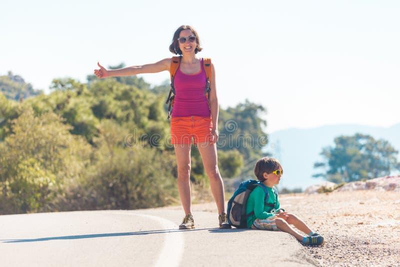 Γυναίκα με να κάνει ωτοστόπ παιδιών στοκ εικόνα