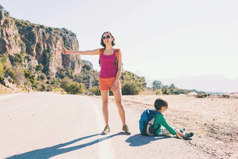 Γυναίκα με να κάνει ωτοστόπ παιδιών στοκ εικόνες
