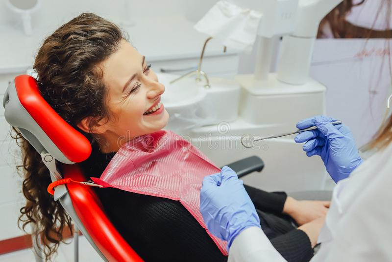 Γυναίκα στην υποδοχή ενός οδοντιάτρου σε μια οδοντική κλινική Κάθεται σε μια κόκκινη καρέκλα Ευτυχής έννοια ασθενών και οδοντιάτρ στοκ φωτογραφία με δικαίωμα ελεύθερης χρήσης