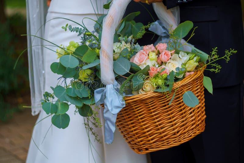 Γυναίκα στο άσπρο φόρεμα που κρατά ένα καλάθι των λουλουδιών κανένα πρόσωπο στοκ φωτογραφία