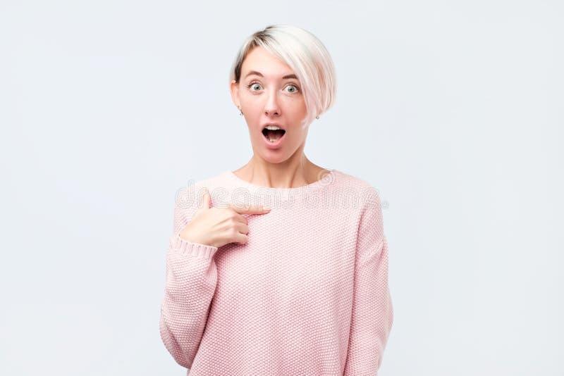 Γυναίκα στο ρόδινο πουλόβερ που δείχνει σε την στον ενθουσιασμό που είναι ευχαριστημένο από τα succes στοκ φωτογραφία