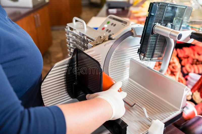 Γυναίκα στο τέμνον μπέϊκον καταστημάτων χασάπηδων με τη μηχανή στοκ φωτογραφίες