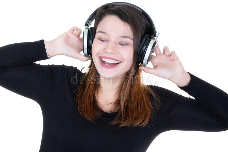 Γυναίκα που ακούει τη μουσική στα ακουστικά ακουστικών που απολαμβάνουν και που τραγουδούν στοκ εικόνες με δικαίωμα ελεύθερης χρήσης