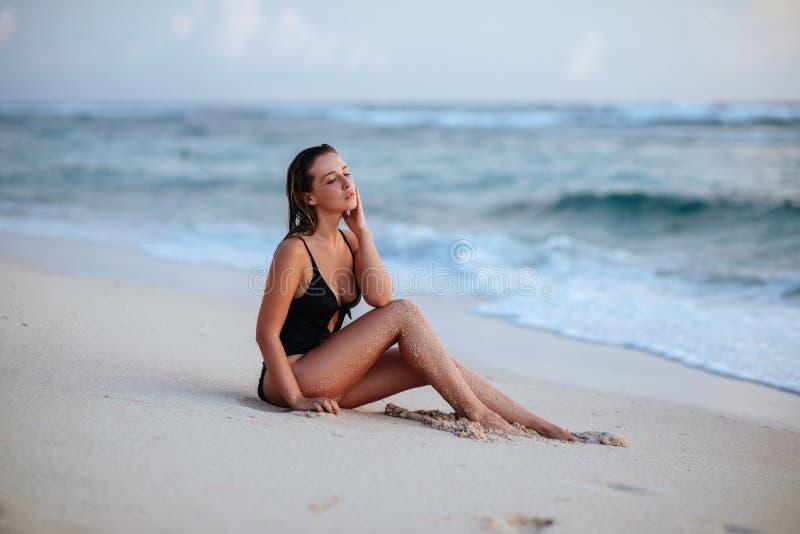 Γυναίκα που απολαμβάνει το όμορφο ηλιοβασίλεμα στην παραλία στοκ εικόνες