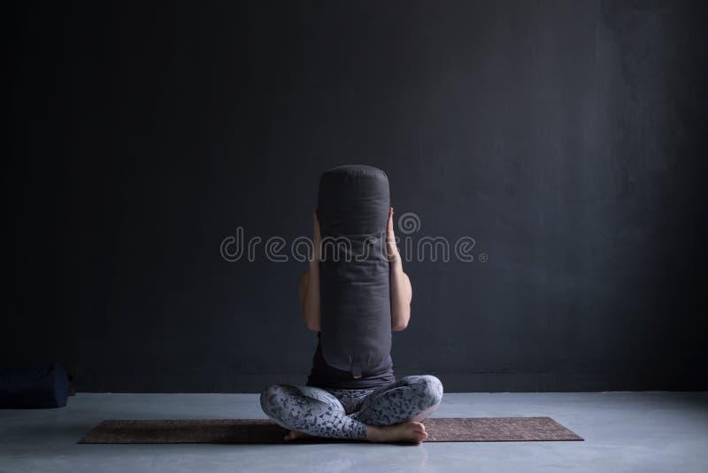 Γυναίκα που κάνει τη γιόγκα στο στούντιο που κρύβει το πρόσωπό της με το bloster στοκ εικόνα με δικαίωμα ελεύθερης χρήσης