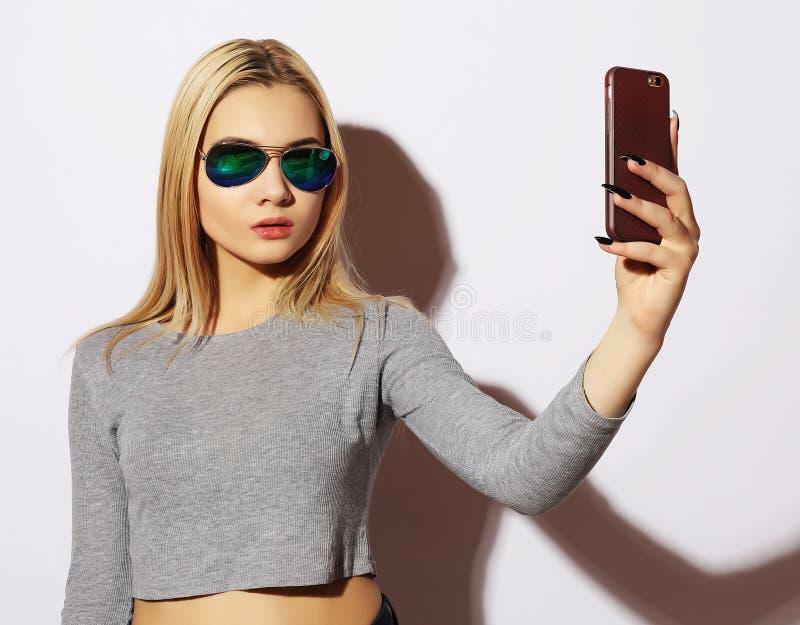 γυναίκα που κάνει selfie τη φωτογραφία στο smartphone που απομονώνεται σε μια λευκιά ΤΣΕ στοκ εικόνες