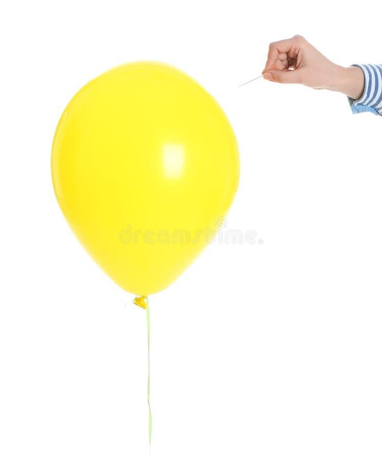 Γυναίκα που διαπερνά το κίτρινο μπαλόνι στο άσπρο υπόβαθρο στοκ φωτογραφία με δικαίωμα ελεύθερης χρήσης