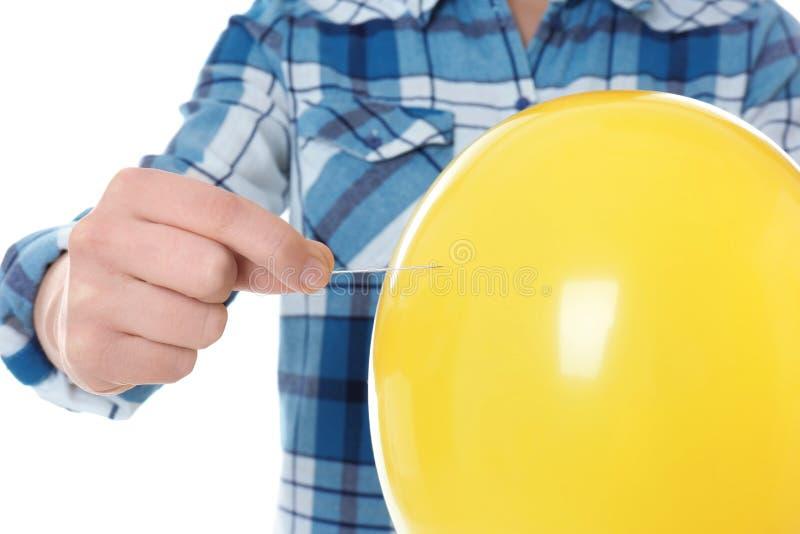 Γυναίκα που διαπερνά το κίτρινο μπαλόνι στο άσπρο υπόβαθρο στοκ εικόνες