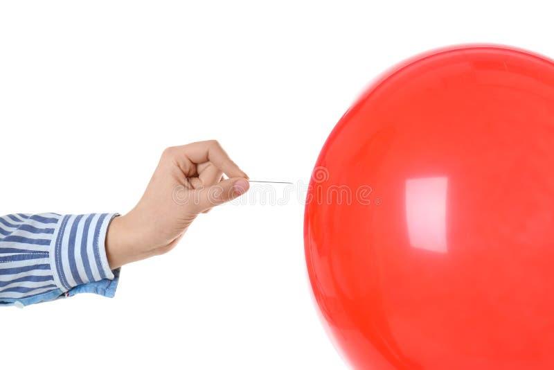 Γυναίκα που διαπερνά το κόκκινο μπαλόνι στο άσπρο υπόβαθρο στοκ εικόνα με δικαίωμα ελεύθερης χρήσης