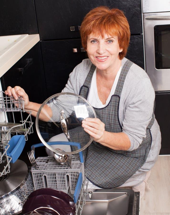 Γυναίκα που διπλώνει τα πιάτα στο πλυντήριο πιάτων στοκ φωτογραφίες με δικαίωμα ελεύθερης χρήσης